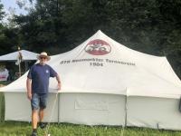 Der stolze Obmann vor dem Zelt