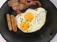 Frühstück serviert Spiegeleier Frühstücksspeck und gebratene Würstchen