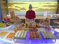Bordbäckerin beim Frühstücksbrotbuffet